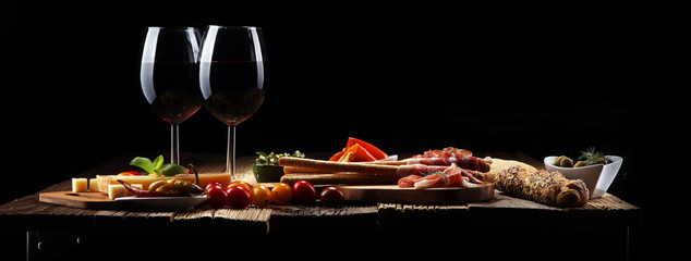 Poster Vin Italian antipasti wine snacks set. Cheese variety, Mediterranean olives, crudo, Prosciutto di Parma, salami and wine in glasses over wooden grunge background.