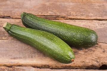 Ripe green zucchini on wood. Old vintage rustic wooden table.