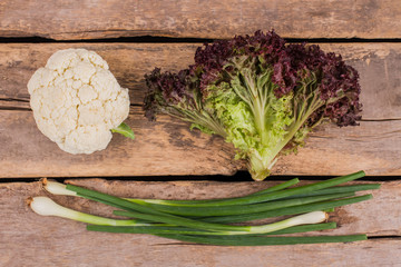 Raw green onion, cauliflower and purple lettuce. Top view. Old vintage wooden background.