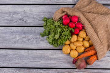 Bag with different vegetables on wood. Free space for text. Copy space.