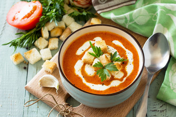 Diet menu. Puree soup tomato with croutons and cream in a bowl on a kitchen wooden table. The concept of healthy eating.