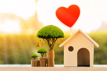 House model and red heart for family and stack coin and money bag of tree as destinations on the top put on the wood in the morning sunlight, Business investment or loan for real estate concept.