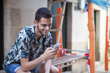 young man with mobile phone in the street of the city smiling and typing or reading