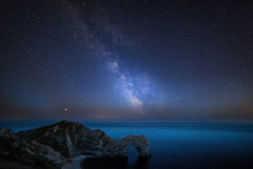 Beautiful vibrant image of Milky Way galaxy over sea landscape in Dorset England