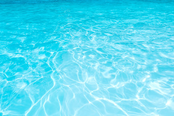 Pattern of blue water surface in swimming pool, Ripple wave and motion water for blue background and abstract, Bright and purified water with sun reflection in pool