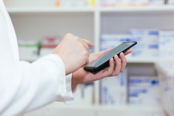 Pharmacist, Physician using a mobile phone at drugstore room. Doctor touching a cell phone in medical concept.