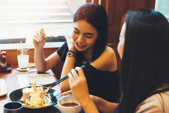 Two young attractive Asian women eating Shrimp Tempura Japanese food at restaurant with happiness and joy