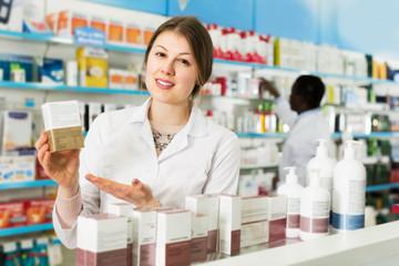 Female pharmacist offering medication