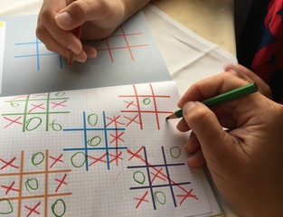 Mum and kid playing tic tac toe in travel