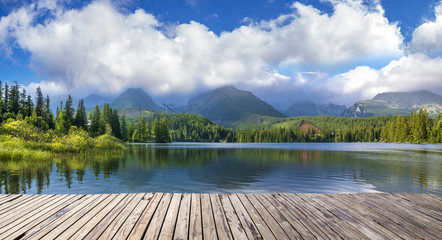 Wooden path on alpine lake Strbske Pleso with reflection of mountains, sky and clouds in the calm water, High Tatras, Slovakia