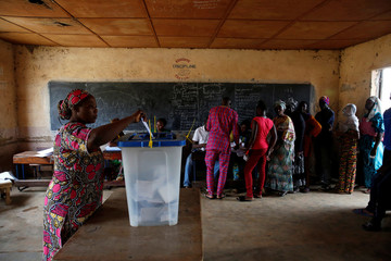 A woman casts her vote at a polling station during the presidential election in Bamako