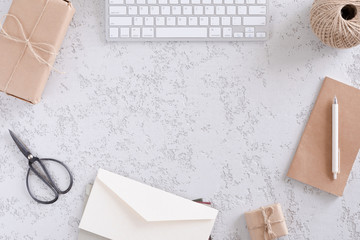 Top view of office stationery and accessories, gift boxes, envelope and cup of latte coffee . Minimalistic flat lay, vintage styled home office desk workspace