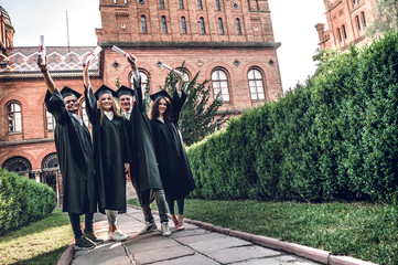 Ready to bright future! Four college graduates showing their diplomas and smiling while standing in university.