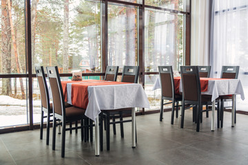 Dining tables and chairs in the restaurant. Big windows. Light interior