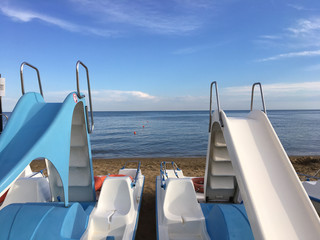 Pedal boat (Pedalò) with slides and deck chairs, in calm blue sea background with white clouds on the horizon