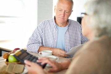Mature man with papers and his wife with calculator counting their expenses