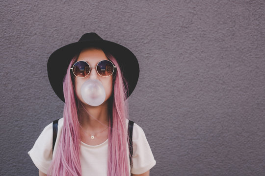 Young hipster woman with long pink hair blowing a bubble with bubble gum.