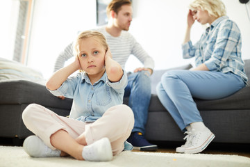 Cross-legged little girl sitting on the floor and covering her ears while parents having quarrel