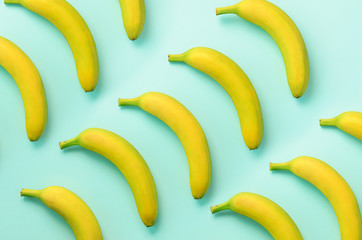 Colorful fruit pattern. Bananas over blue background. Top view. Pop art design, creative summer concept. Minimal flat lay style.