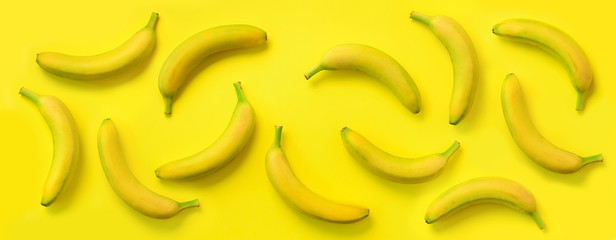 Chaotic colorful fruit pattern. Bananas over yellow background. Banner. Top view. Pop art design,...