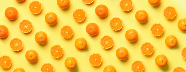 Fruit pattern of fresh orange slices on yellow background. Top view. Copy Space. Pop art design,...