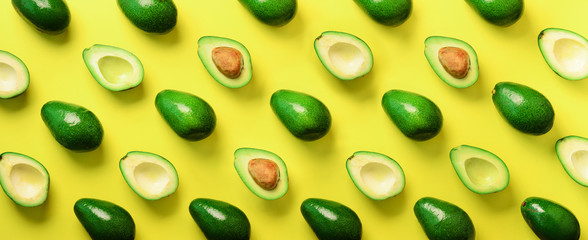 Avocado pattern on yellow background. Top view. Banner. Pop art design, creative summer food concept. Green avocadoes, minimal flat lay style. Banner