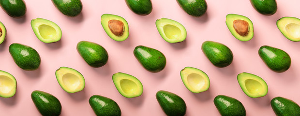Avocado pattern on pink background. Top view. Banner. Pop art design, creative summer food concept. Green avocadoes, minimal flat lay style. Banner