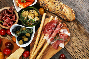 Fotobehang Picknick Italian antipasti wine snacks set. Cheese variety, Mediterranean olives, crudo, Prosciutto di Parma, salami and wine in glasses over wooden grunge background.