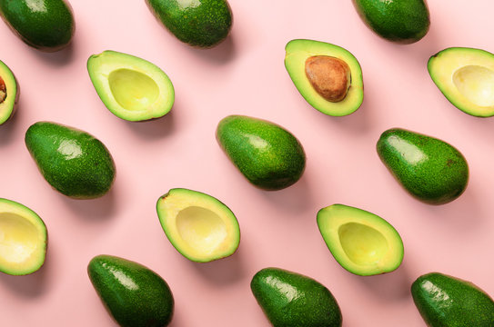 Avocado pattern on pink background. Top view. Banner. Pop art design, creative summer food concept. Green avocadoes, minimal flat lay style.