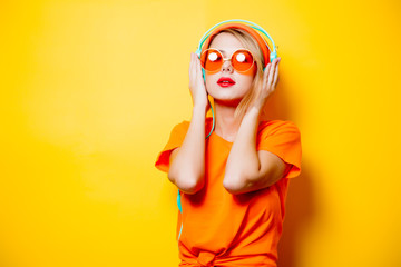 Young style girl with orange glasses and headphones on yellow background. Clothes in 1980s style