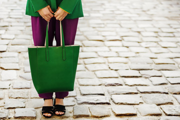 Fashion details: big leather green tote bag in hands of fashionable woman. Model posing in street of european city. Copy, empty space for text