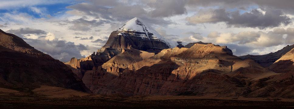 Mount Kailash, Kangrinboqe peak. Ngari, Tibet Autonomous Region of China. Panoramic view with Sunset, dramatic lighting, snow mountain peaks illuminated. Tibetan pilgrimage site, Sacred Mountain
