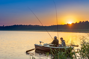 father and son catch fish from a boat at sunset Fototapete