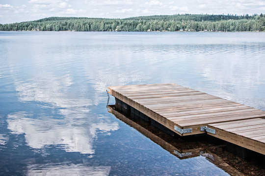 landscape of wooden dock floating in lake at sweden countryside