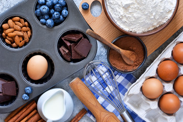 Food background. Ingredients for baking: flour, eggs, berries, chocolate on a concrete background.