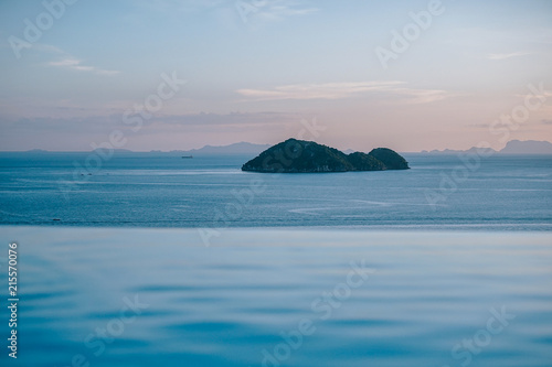 Scenic View Of Sunset From Infinity Pool Overlooking Calm Sea Water With Fishing Boats Around The