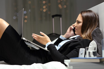 Angry businesswoman complaining on phone in an hotel