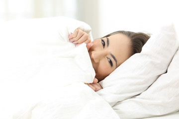 Woman hiding face on the bed