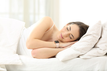 Woman sleeping on the bed wearing a smartwatch