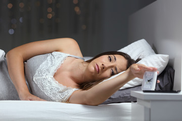 Woman waking up in the night turning off alarm clock