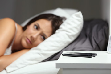 Worried woman waiting for a phone call in the night
