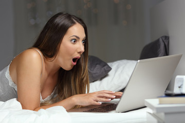 Amazed woman reading good news online in the night