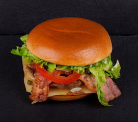 Fresh tasty burger, on black stone background.