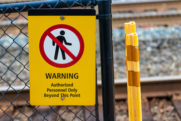Warning authorized personnel sign on a chain link fence