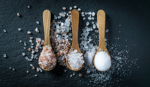 Different types of salt. Top view on three wooden spoons