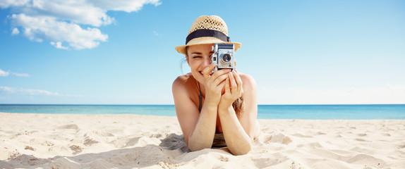 happy woman taking photo with retro photo camera on seacoast