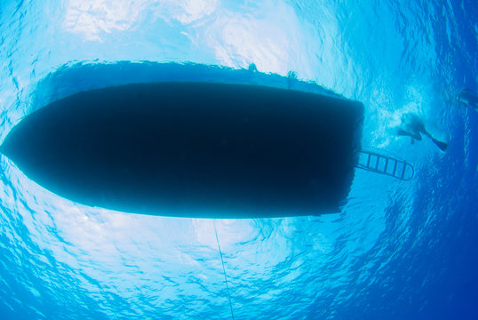 A shot taken from the underside of a scuba dive boat. The vessel is floating on the surface of the calm Caribbean sea and the sun can be seen above as well as divers dropping off the back