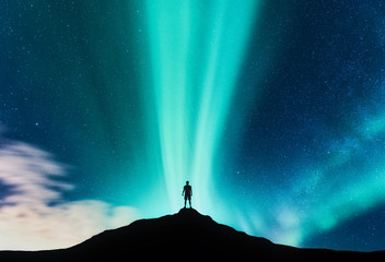 Aurora borealis and silhouette of standing man on the mountain. Aurora and traveller. Starry sky and green polar lights. Night landscape with northern lights and people. Concept. Nature background