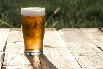 Obraz Szklanka piwa na drewnianym blacie. - fototapety do salonu