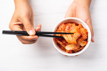 Hand holding kimchi cabbage in a bowl and chopsticks for eating, top view, Korean food